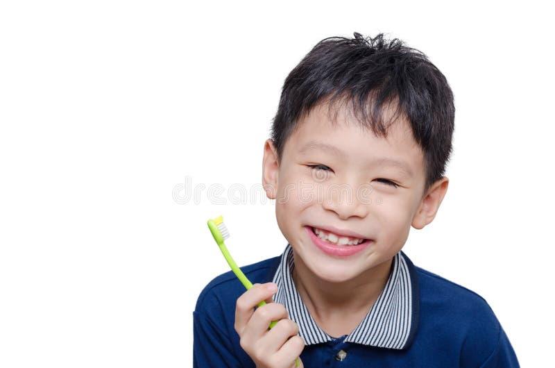 Spazzolino da denti e sorrisi della tenuta del ragazzo fotografie stock libere da diritti