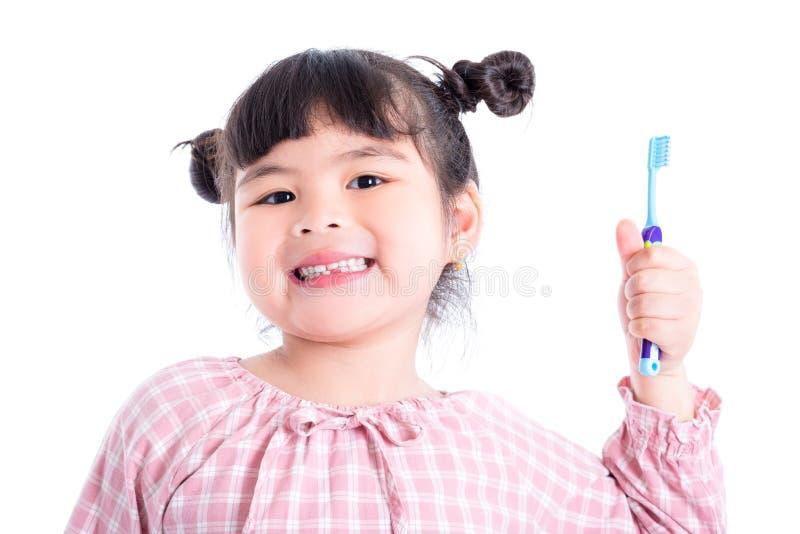 Spazzolino da denti e sorrisi della tenuta della ragazza sopra bianco fotografie stock libere da diritti