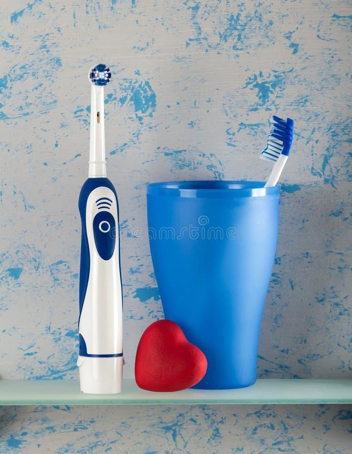 Spazzolino da denti elettrico e ed usuale in vetro, piccolo cuore fotografia stock