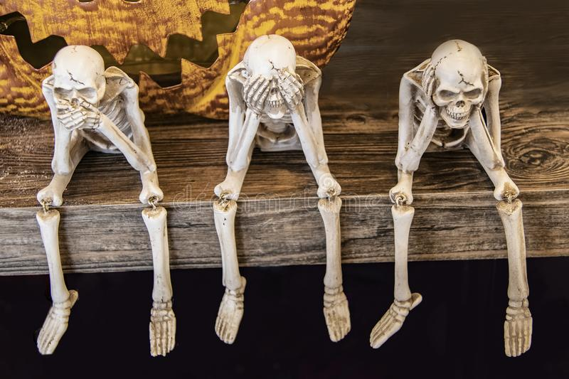 Speak no evil See no evil Hear no evil skeletons sitting on edge of a table with giant scarey metal pumpkin mouth behind them for royalty free stock photography