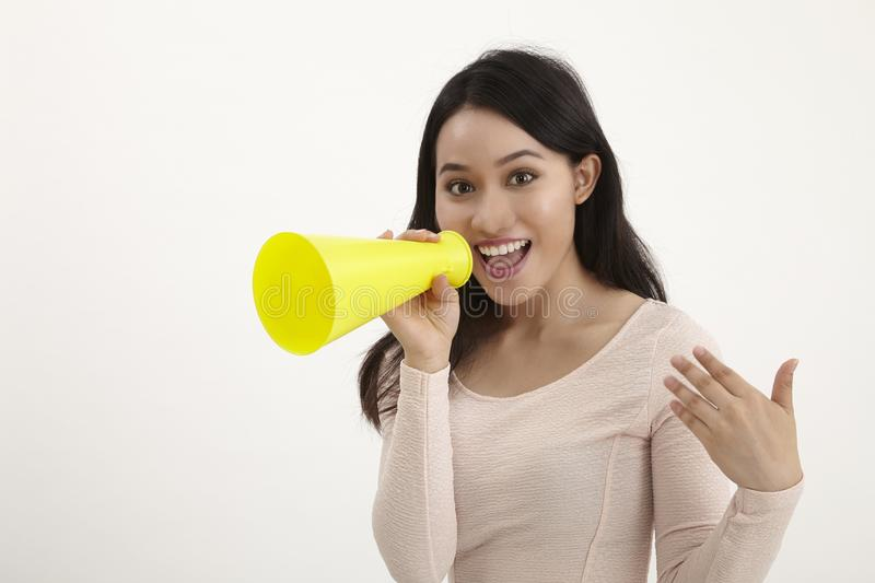 Speak out. Malay woman using megaphone on the white background stock image