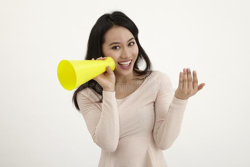 Speak out. Malay woman using megaphone on the white background royalty free stock image