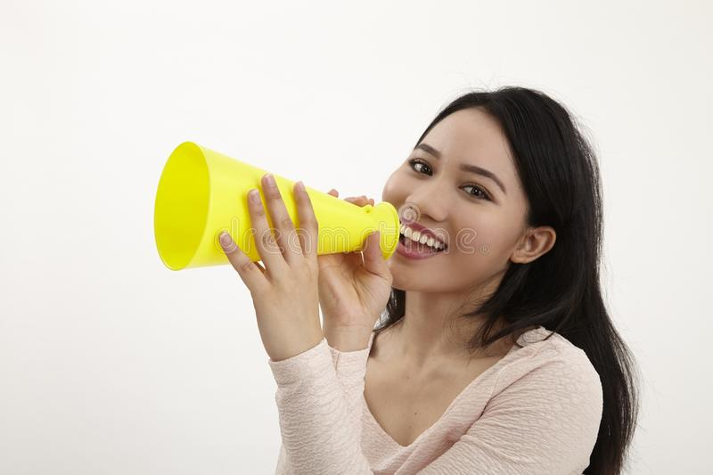 Speak out. Malay woman using megaphone on the white background stock photo