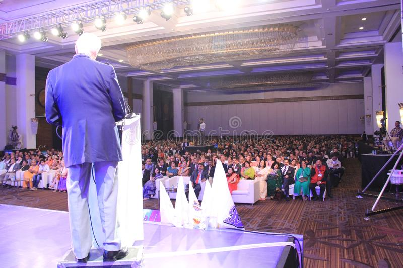 Speaker addressing a house full of conference audience. Chief Guest standing on stage dais and speaking to delegates in a conclave of Rotary International Club stock photography
