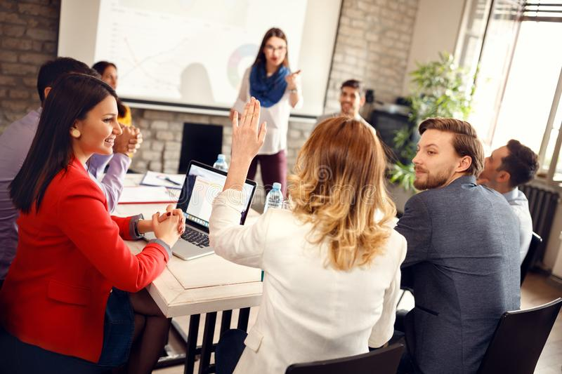 Speaker on business meeting gives word to young woman royalty free stock photo