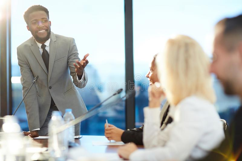 Speaker in front of audience. Happy young African-american speaker explaining to audience his methods and strategies of leading business stock photo