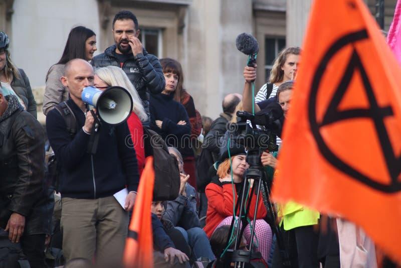 Speaker In Front of Orange Extinction Rebellion flag. stock photo