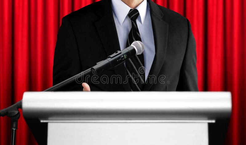 Speaker giving speech at seminar with red curtain background royalty free stock photo