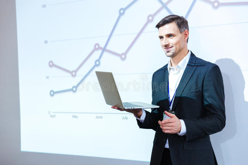 Speaker holding laptop and giving presentation stock photography