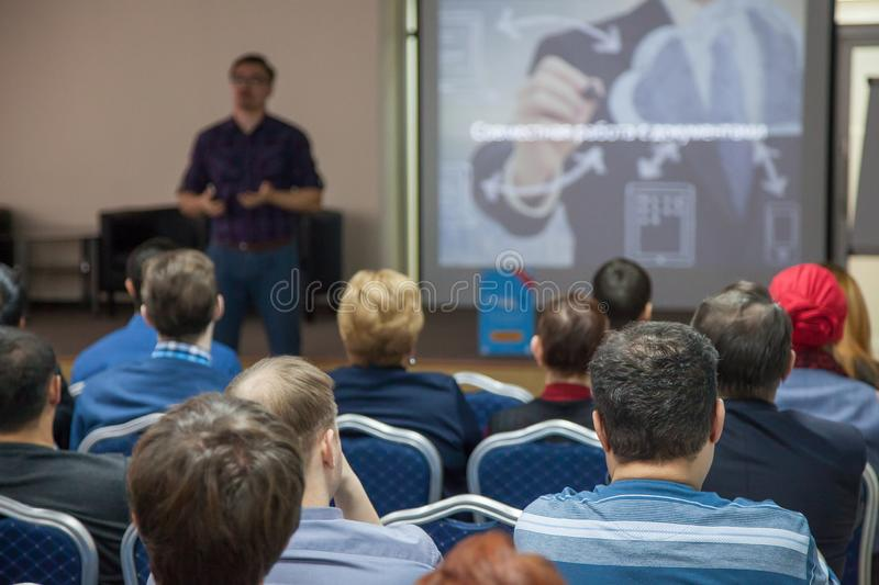 The speaker makes a report at a business meeting. The audience. Business and entrepreneurship, conferences royalty free stock images