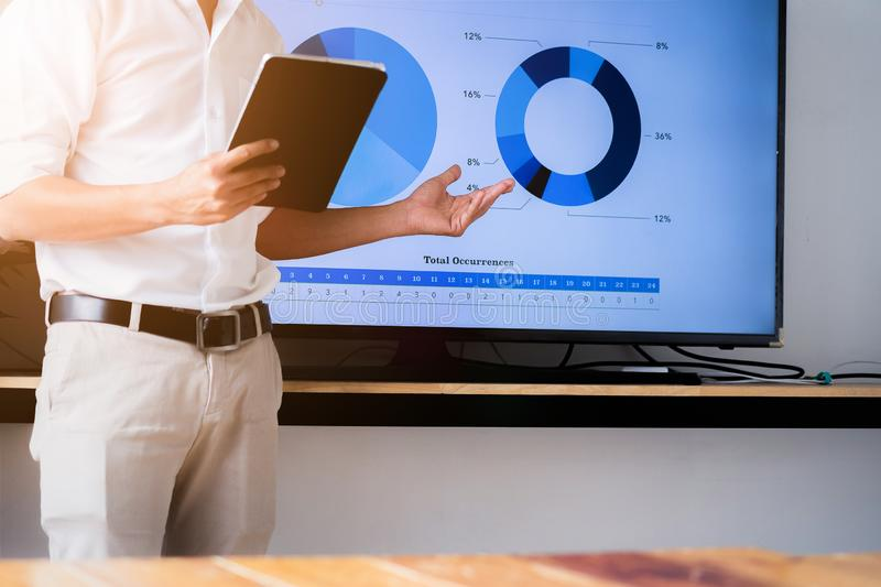 Speaker man talking to audience giving a lecture and holding tablet. Business presentation concept stock image