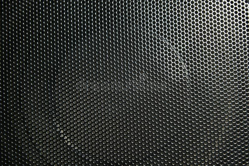 The speaker of a musical column hidden behind a grid with a pattern of rhythmically arranged holes stock photos