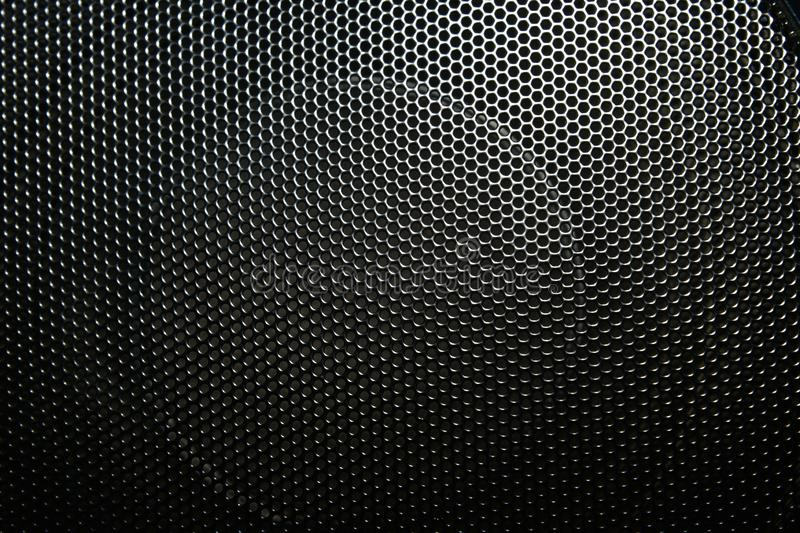 The speaker of a musical column hidden behind a grid with a pattern of rhythmically arranged holes stock images