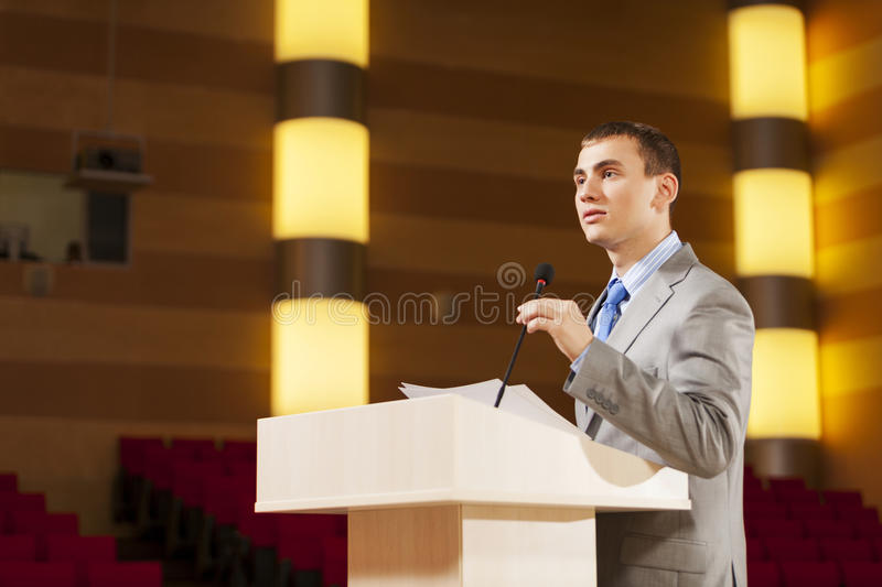 Speaker at stage. Businessman standing on stage and reporting for audience stock photo