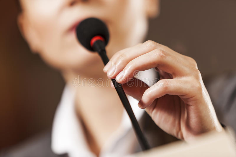 Speaker at stage. Businesswoman standing on stage and reporting for audience stock images