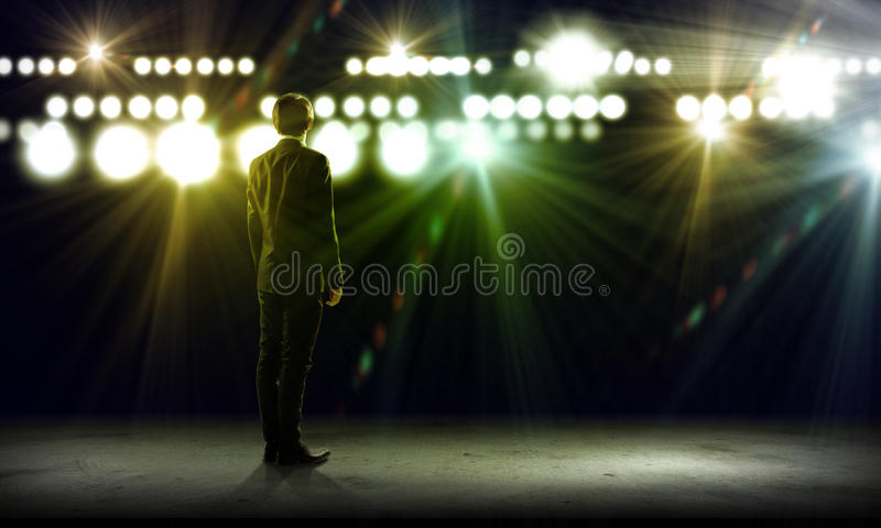 Speaker on stage. Rear view of businessman standing in lights of stage royalty free stock photos