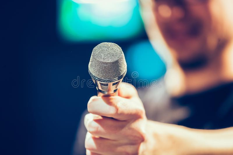 Speaker on the stage: Young Caucasian man is talking into a mirophone, blurry. Young man on the stage is talking into a microphone, speech, face is blurry royalty free stock images