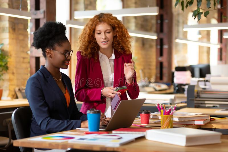Curly assistant of interior designer speaking with her boss. Speaking with boss. Curly red-haired assistant of interior designer speaking with her boss royalty free stock images