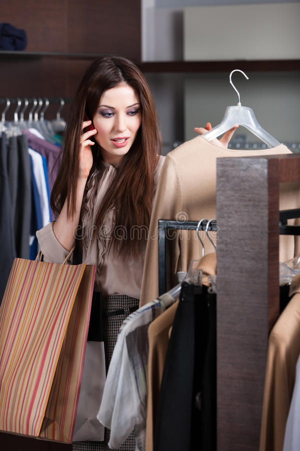 Download Speaking On The Mobile Phone And Choosing Clothes Stock Image - Image: 29528191