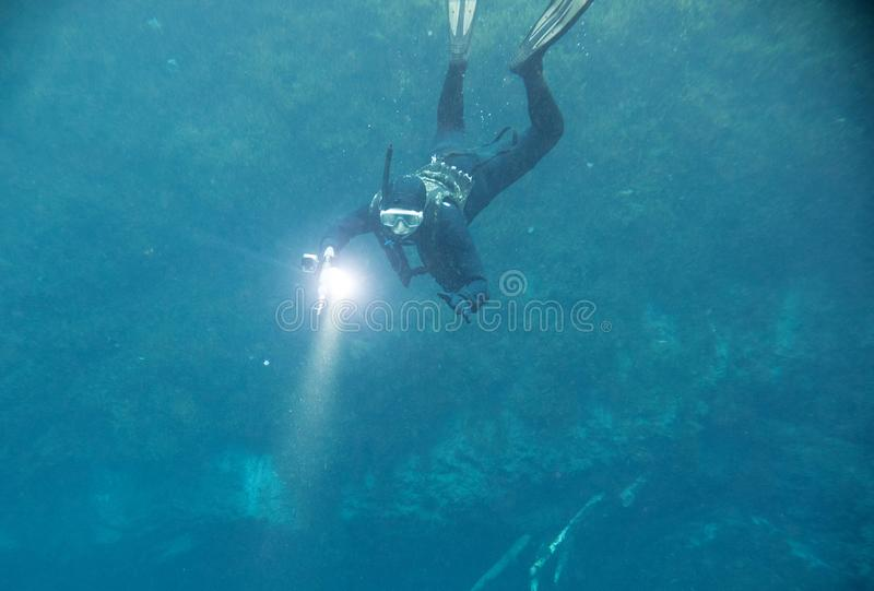 Spearfishing man with flashlight in deep of lake. Underwater shot stock photography