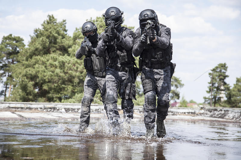 Spec ops警察在水中扑打 免版税库存照片