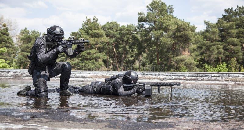 Spec ops警察在水中扑打 库存图片