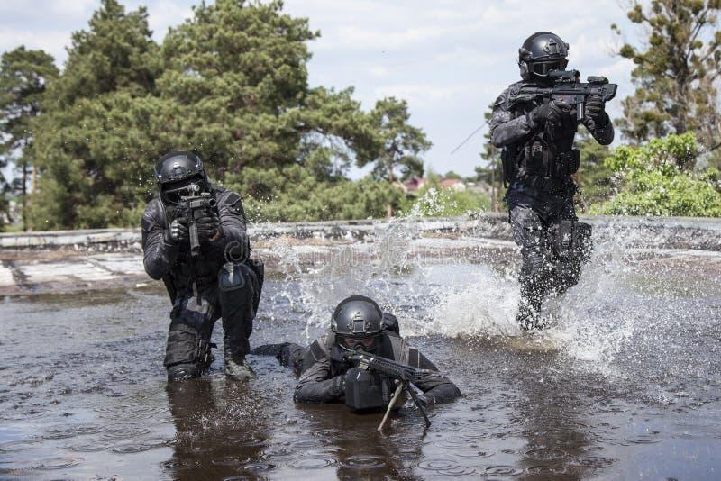 Spec ops funkcjonariuszów policji pacnięcie w wodzie obraz stock