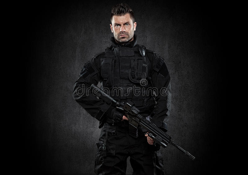 Spec ops police officer SWAT in black uniform studio stock image