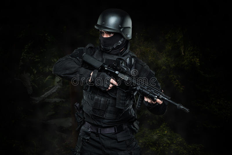Spec ops police officer SWAT in black uniform studio stock photos