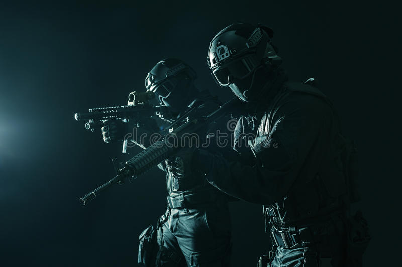 Spec ops police officersSWAT. Spec ops police officers SWAT in black uniform and face mask studio shot stock photos