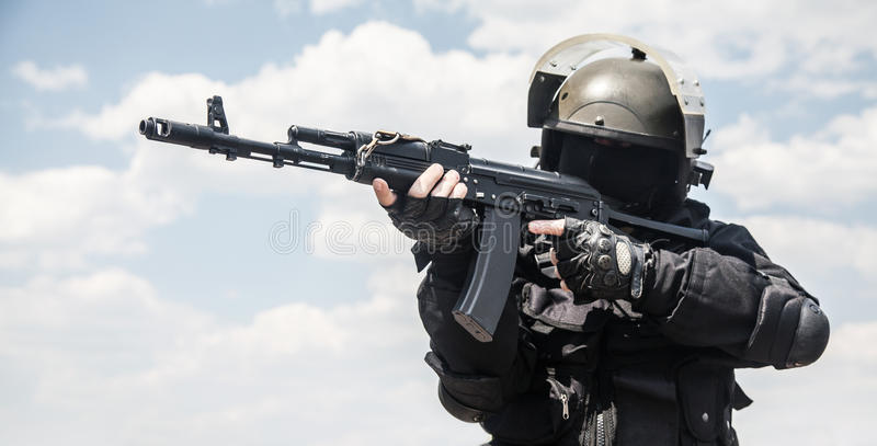Spec ops. Soldier in black uniform and face mask with his rifle stock image