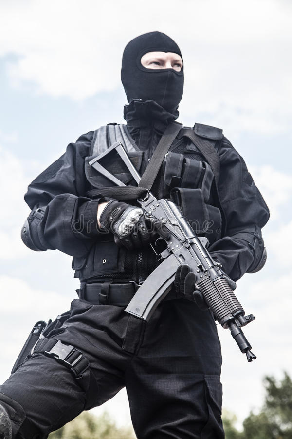Spec ops. Soldier in black uniform and face mask with his rifle stock photo
