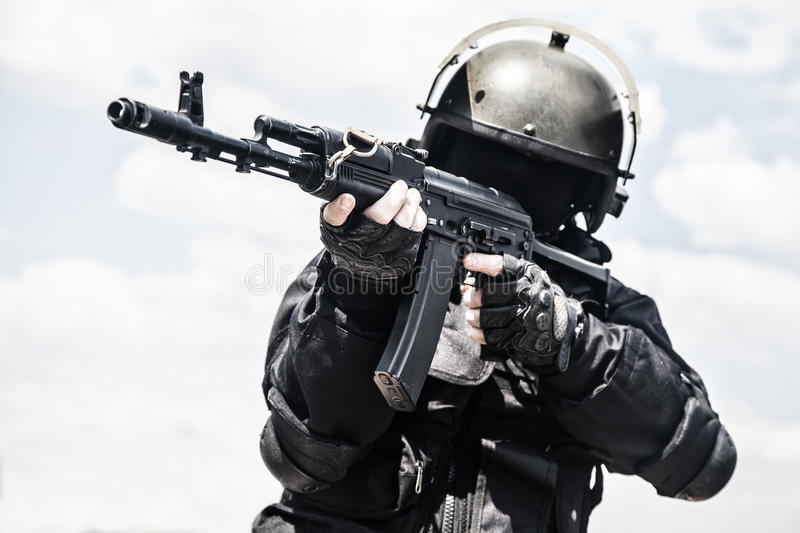 Spec ops. Soldier in black uniform and face mask with his rifle royalty free stock photos