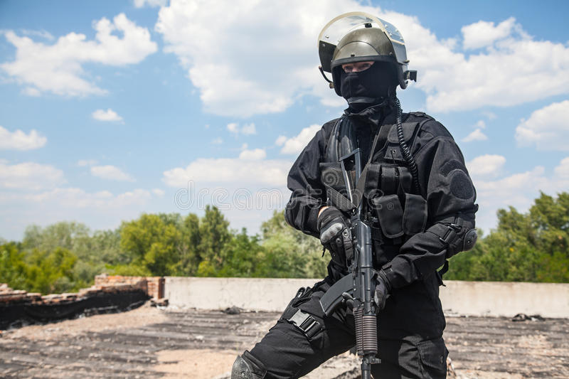 Spec ops. Soldier in black uniform and face mask with his rifle royalty free stock images