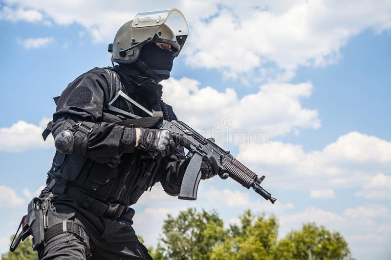 Spec ops. Soldier in black uniform and face mask with his rifle stock photography