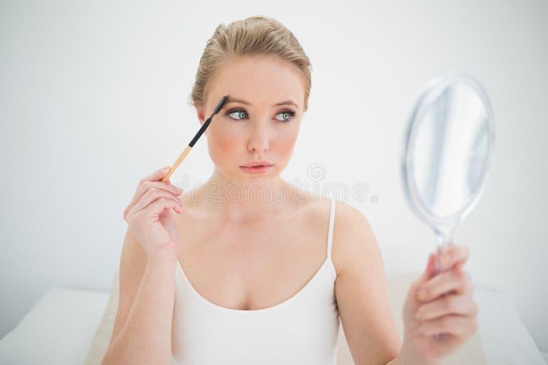 Specchio biondo calmo naturale della tenuta ed usando la spazzola del sopracciglio fotografia stock