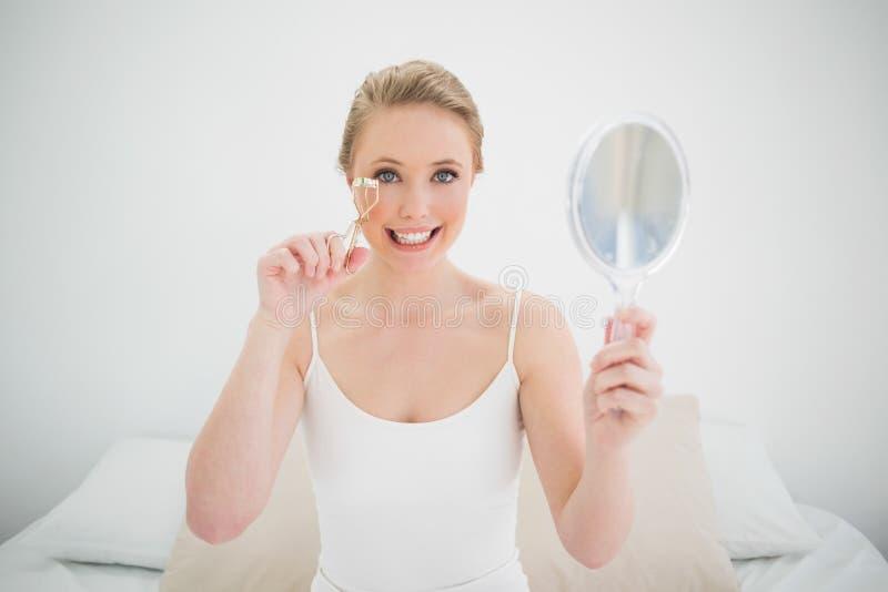 Specchio biondo felice naturale della tenuta e per mezzo del bigodino del ciglio fotografie stock
