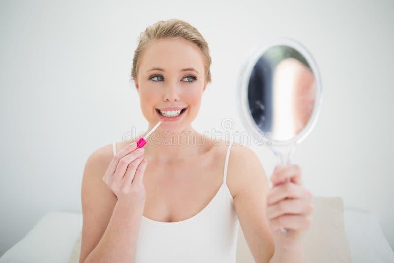 Specchio biondo felice naturale della tenuta ed applicare lucentezza del labbro fotografia stock libera da diritti