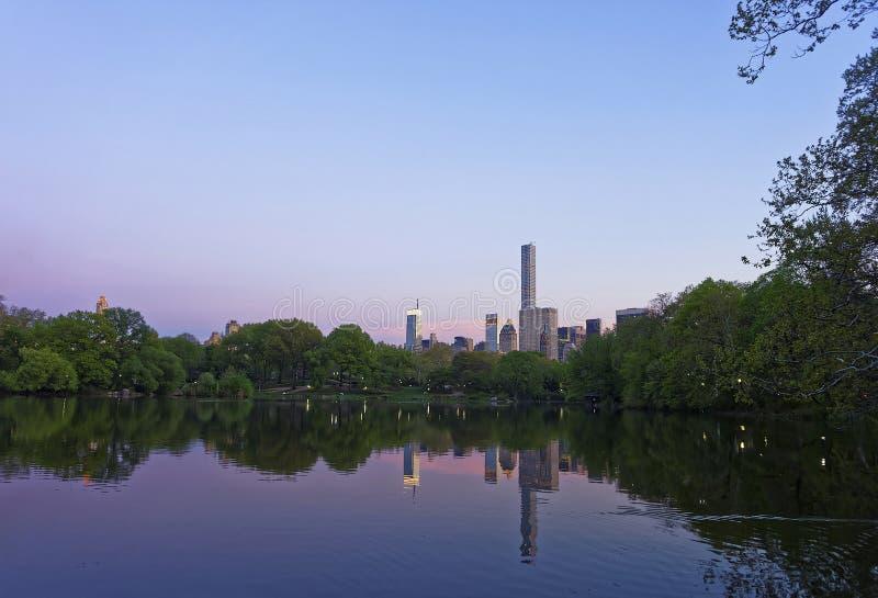 Specchio dell'orizzonte di Manhattan di Midtown da acqua in Central Park immagini stock