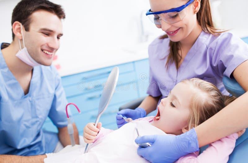 Specchio della tenuta della bambina ai dentisti immagine stock