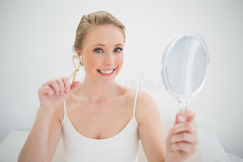 Specchio della tenuta e bigodino biondi sorridenti naturali del ciglio immagine stock libera da diritti