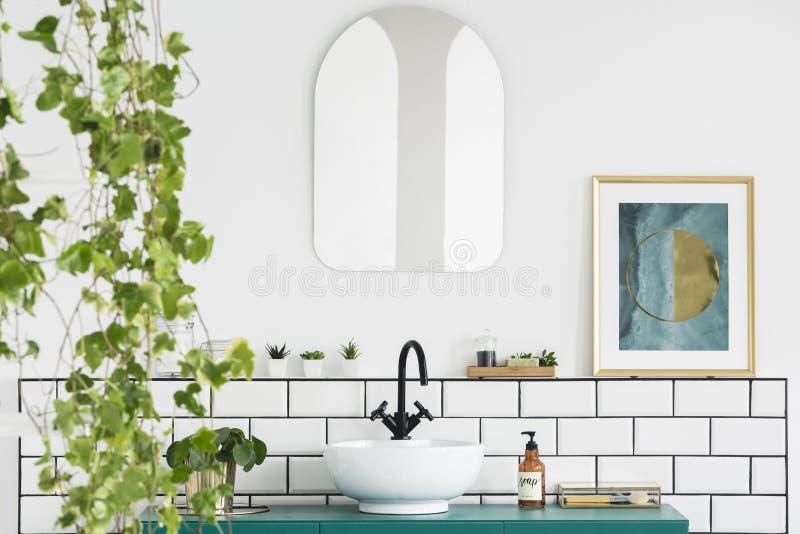 Specchio e manifesto nell'interno bianco del bagno con il lavandino e la pianta Foto reale fotografia stock libera da diritti