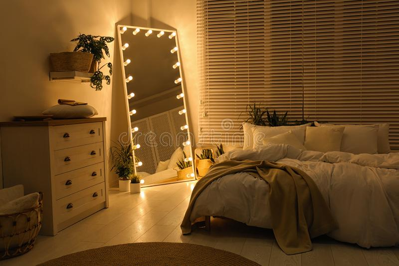 Specchio elegante con lampadine nella camera da letto Design interno immagine stock libera da diritti