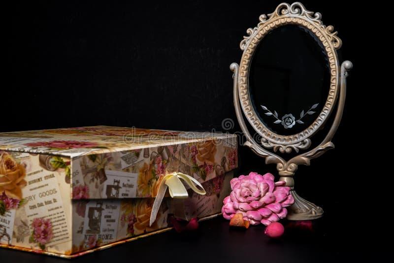 Specchio ovale d'annata dello scrittorio con la struttura bianca, i pezzi dei potpourri e un contenitore di ricordo su fondo nero fotografie stock libere da diritti