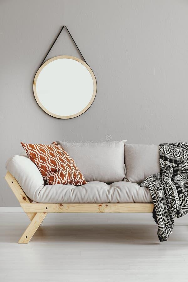 Specchio rotondo che appende sulla parete in salone luminoso interno con il sofà grigio chiaro con il cuscino e la coperta in fot immagini stock libere da diritti