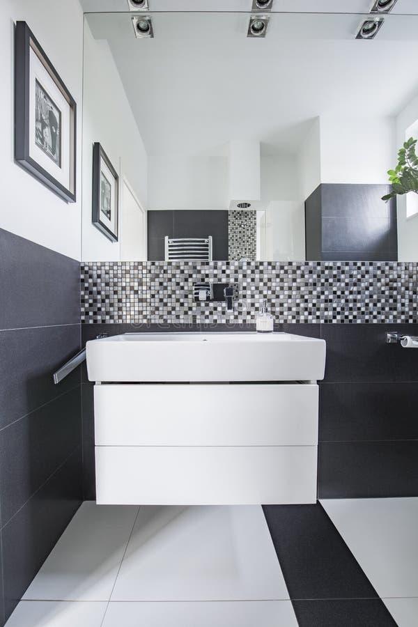 Specchio sopra il lavandino bianco nell'interno moderno del bagno con il manifesto Foto reale fotografia stock