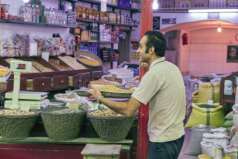 Specerihandlare i en livsmedelsbutik i den östliga marknaden, Kashan, Iran arkivbild