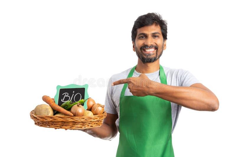 Specerihandlare som framlägger grönsakkorgen med det bio tecknet royaltyfria foton