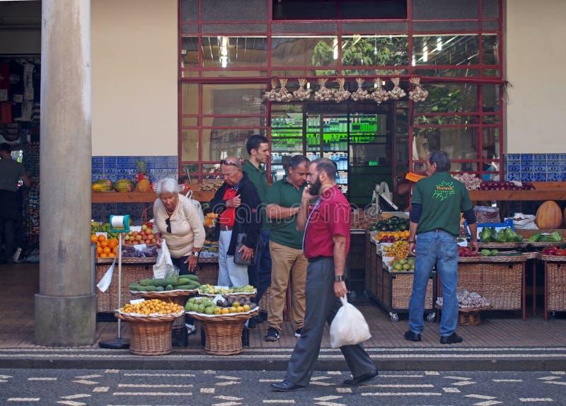 Specerihandlare utanför shoppar sälja frukt och grönsaker i den funchal marknaden i madeira med jordbruksprodukter i korgar som ä royaltyfri foto