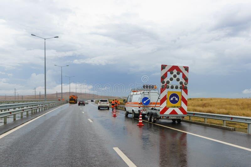 Speciaal en de werknemers van de wegdiensten bij de scène van het ongeval op de weg op een bewolkte de herfstdag royalty-vrije stock fotografie